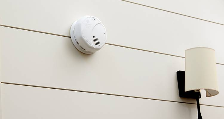 Smoke alarm installed on a decorated wall, next to a wall lamp.